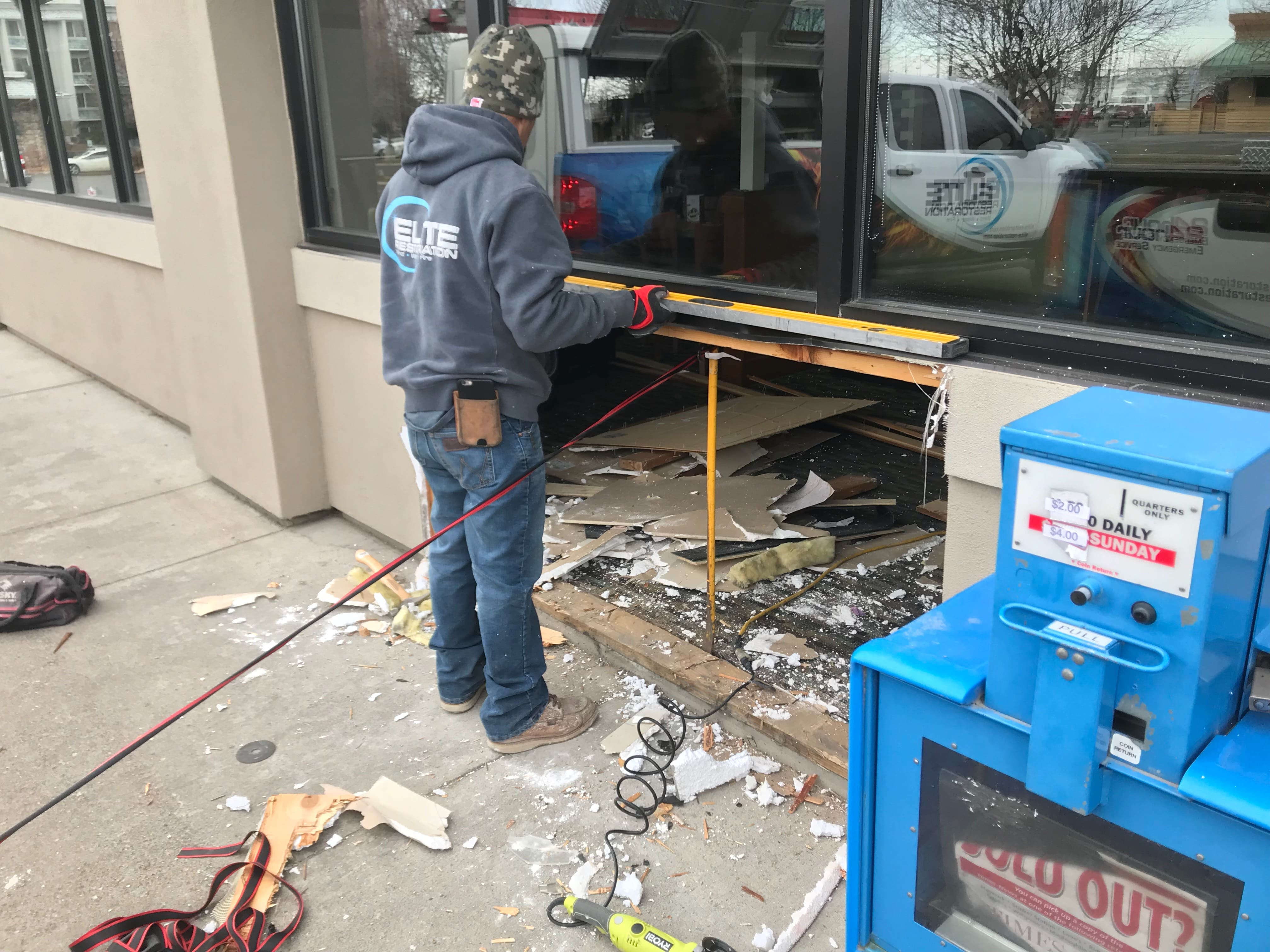 Image: Elite Restoration Tech works at repairing a car sized hole in a Perkins restaurant.