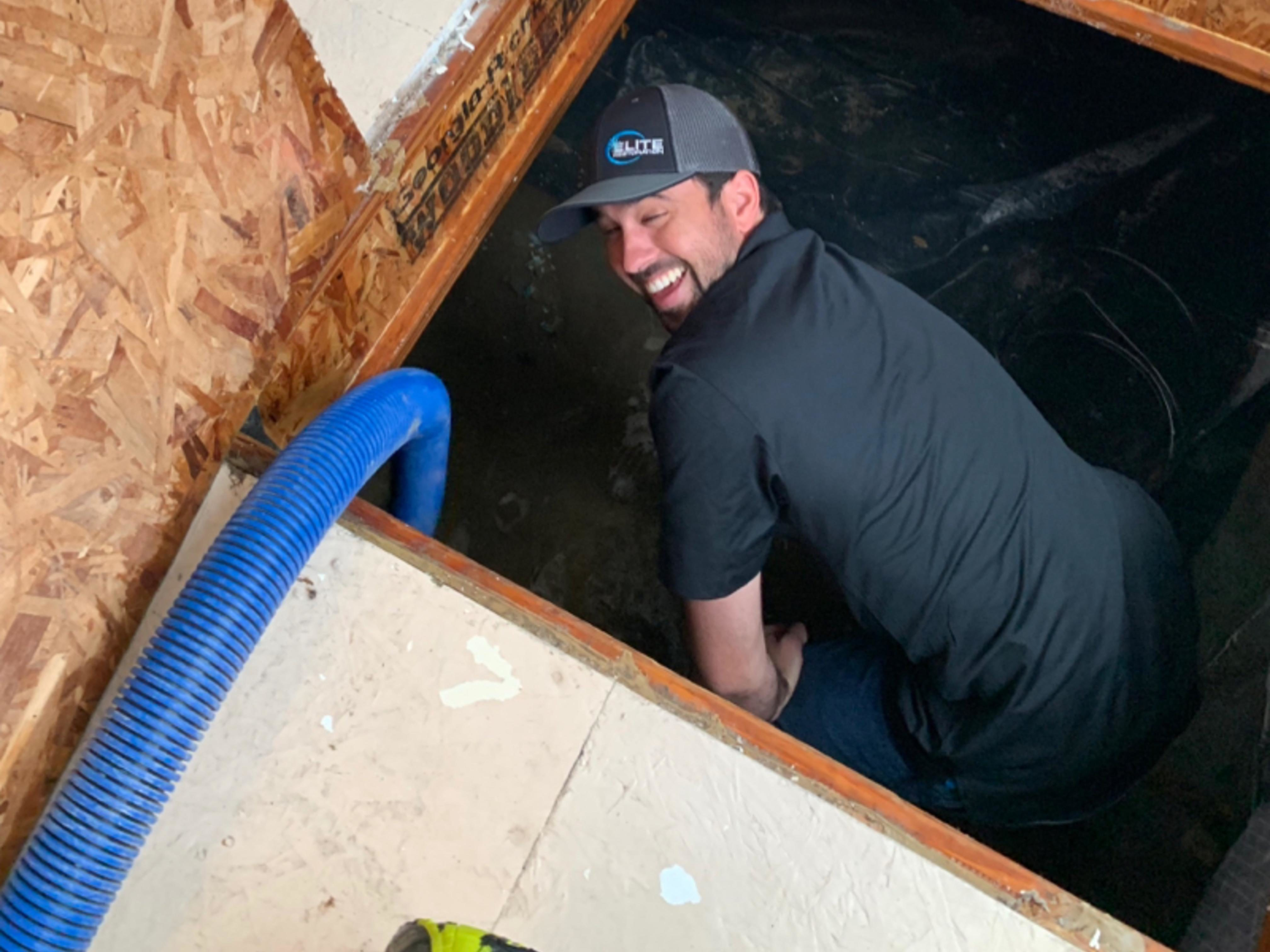 Image: Elite Restoration tech smiling up from a crawlspace at the Morrison Funeral Home.