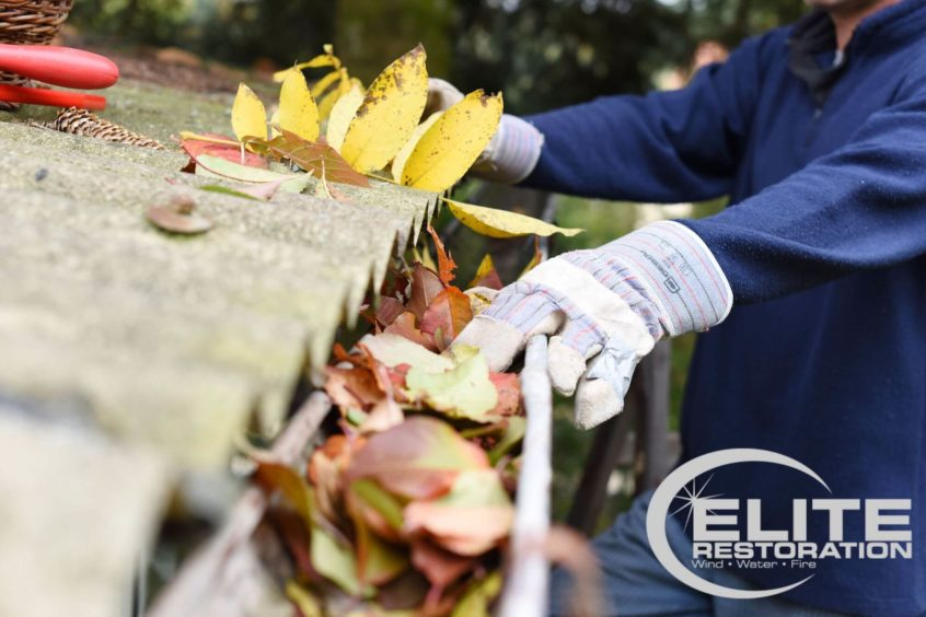 man-cleaning-leaves-out-of-gutter